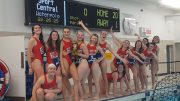 Women's water polo team stood at side of pool celebrating win